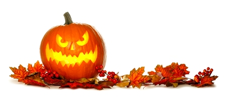 Illuminated Halloween Jack o Lantern with border of red autumn leaves isolated on a white background Stock Photo