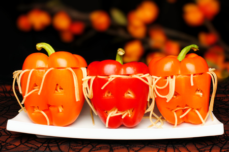 Halloween stuffed pepper monster heads on a plate with dark background