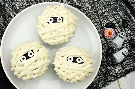 Group of Halloween mummy cupcakes on white plate with candies on black cloth background
