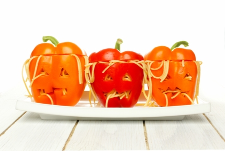 Halloween monster head stuffed peppers on a plate with white wood background Stock Photo