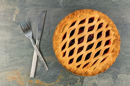 dessert fork: Strawberry and rhubarb pie with fork and knife on a grey slate background Stock Photo