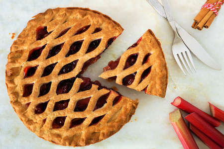 Strawberry and rhubarb pie with cut piece on a marble background overhead scene