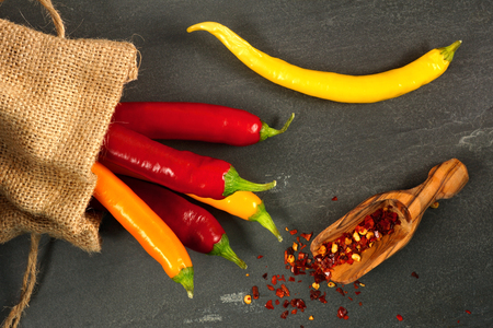 pepper flakes: Multicolored hot peppers spilling from burlap bag with scoop of hot pepper flakes