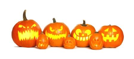 pumpkin border: Row of fun lit Halloween Jack o Lanterns isolated on a white background Stock Photo
