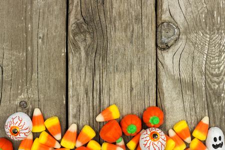 candies: Dulces de Halloween borde inferior sobre un fondo de madera rústica