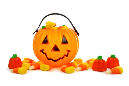 treat: Cute Halloween Jack o Lantern candy collector with scattered candy pumpkins and candy corn over white Stock Photo