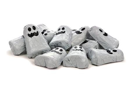 treats: Pile of Halloween chocolate candy ghosts over a white background