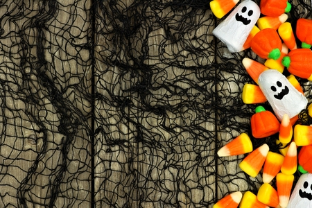 candy: Halloween candy side border against a rustic wood and black cloth background Stock Photo