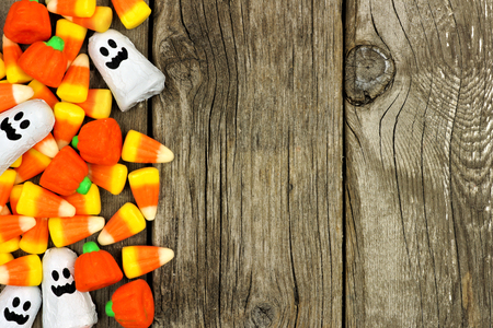 treat: Halloween candy side border against a rustic wood background
