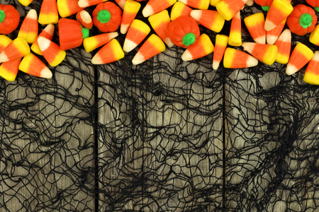 candy border: Halloween candy top border against a rustic wood and spooky black cloth background Stock Photo