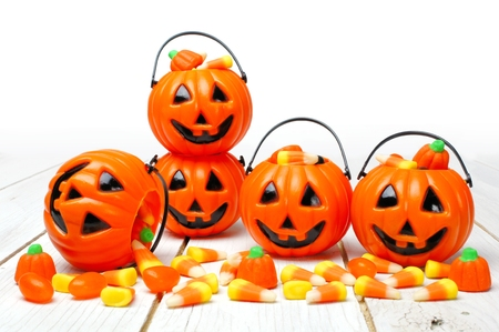 arrangment: Halloween Jack o Lantern candy holders with scattered candy pumpkins and candy corn on white wood