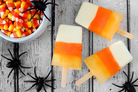 mazorca de maiz: Halloween de paletas de maíz de caramelo ver a la baja sobre viejo fondo de madera blanca con arañas de juguete