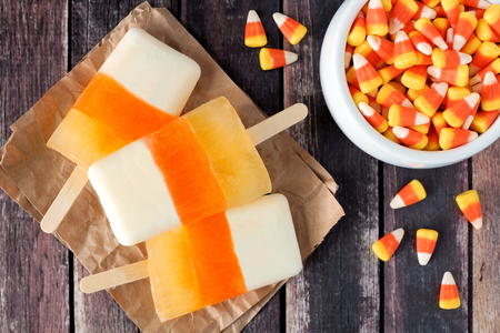 downward: Halloween candy corn popsicles downward view on rustic wood background with bowl of candy