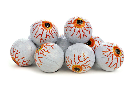 tricks: Pile of Halloween candy eyeballs over a white background