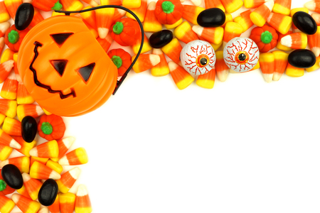 arrangment: Halloween Jack o Lantern candy holder with corner border of candy corn and other treats over white