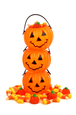 arrangment: Stack of Halloween Jack o Lantern candy holders with pile of candy pumpkins and candy corn over white