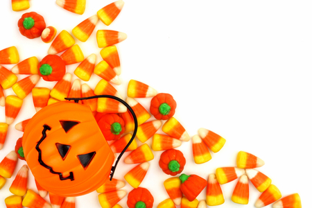 arrangment: Halloween Jack o Lantern candy holder with candy pumpkins and candy corn corner border over white