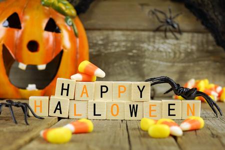 Happy Halloween Holzblöcke mit Süßigkeiten und Dekoration gegen eine alte Holz Hintergrund