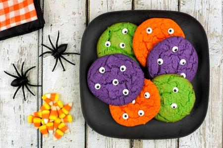 treats: Spooky galletas monstruo de Halloween del globo ocular en un plato sobre fondo de madera rústica con maíz dulce y arañas Foto de archivo
