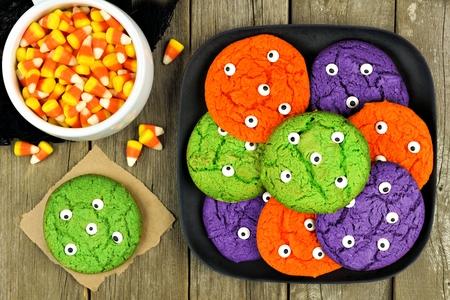 treats: Coloridos de Halloween galletas globo ocular monstruo en un plato negro sobre fondo de madera rústica con maíz dulce