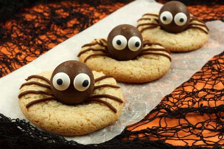 halloween eyeball: Halloween spider cookies on paper with orange and black background Stock Photo