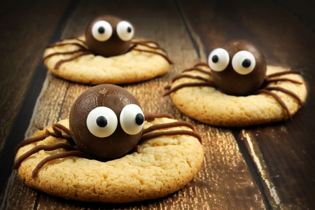 autumn food: Group of chocolate Halloween spider cookies on rustic old wood