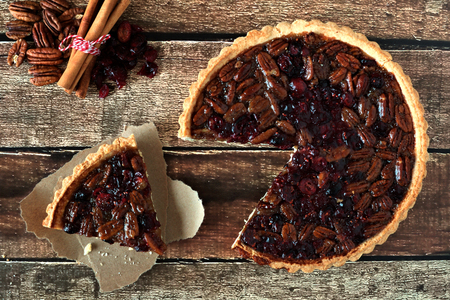 Pecan and cranberry autumn pie, overhead table scene with cut slice on rustic wood 스톡 콘텐츠