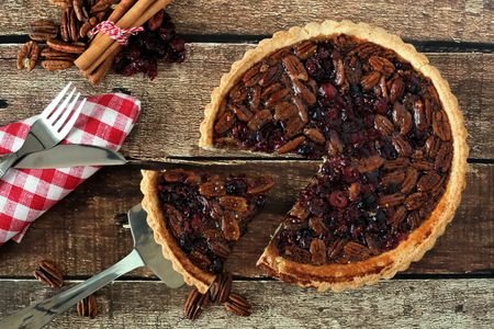Pecan and cranberry autumn pie, overhead table scene on rustic wood with slice being removed 스톡 콘텐츠