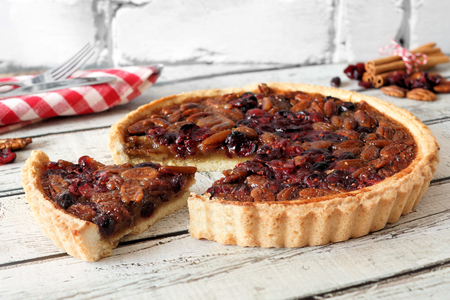 Pecan and cranberry autumn pie with slice removed on rustic white wood