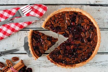 pecan pie: Pecan y el arándano otoño escena tabla de arriba pastel sobre madera blanca con la rebanada se retira