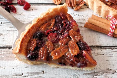 pecan pie: Rebanada de pastel de pacana y el arándano dulce en el servidor con el fondo de madera vieja Foto de archivo