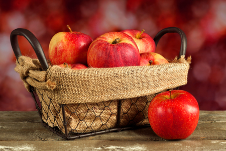 sackcloth: Fresh apples in a wire basket with defocused autumn background