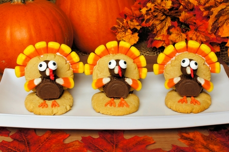 candy corn: Three Thanksgiving turkey shaped cookies on a plate with autumn leaves and pumpkins