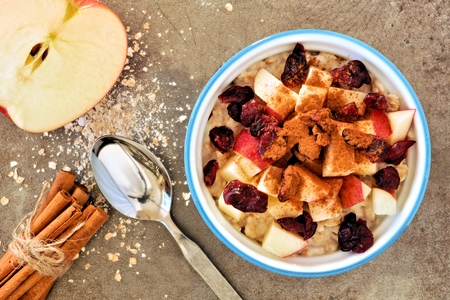 downward: Autumn inspired oatmeal with apples and cranberries, overhead scene on a rustic metal background Stock Photo