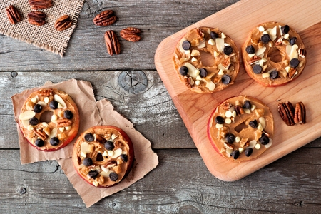 Autumn apple rounds with peanut butter chocolate chips and nuts downward view on rustic wood