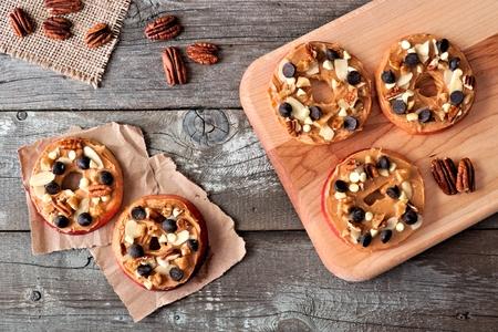 mantequilla: Redondea manzana otoño con chispas de chocolate de mantequilla de maní y vista a la baja tuercas en madera rústica Foto de archivo