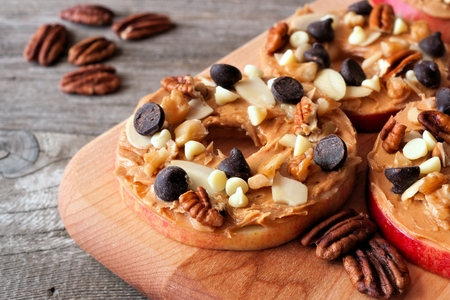butter: Autumn apple rounds with peanut butter, chocolate chips and nuts on a wooden paddle board