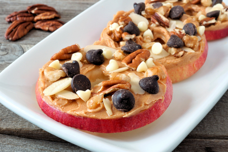 Autumn apple rounds with peanut butter, chocolate chips and nuts, on white serving plate