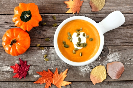 soup: Creamy butternut squash soup topped with pumpkin seeds and cream on rustic wood background with autumn leaves