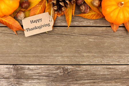 Happy Thanksgiving tag with autumn top border of pumpkins, leaves and nuts on a rustic wooden background
