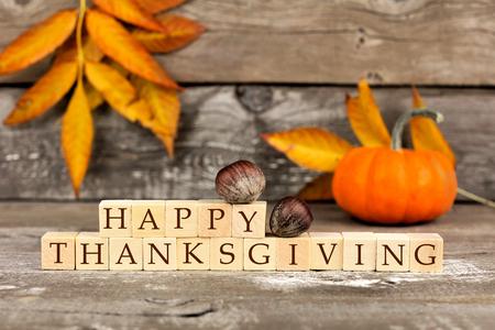 glücklich: Happy Thanksgiving Holzblöcke vor einem rustikalen Holz Hintergrund mit Kürbissen und Herbstlaub
