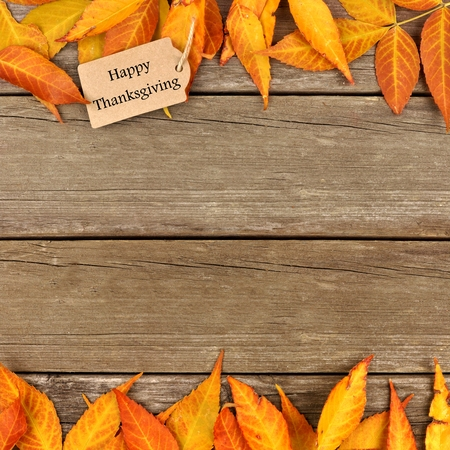 retro background: Happy Thanksgiving gift tag with double border of colorful autumn leaves on a rustic wooden background
