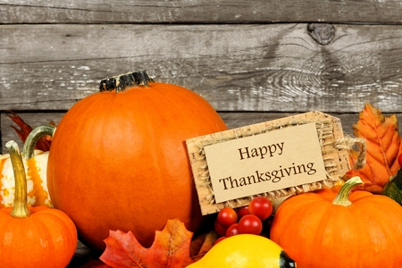Autumn pumpkins with Happy Thanksgiving tag against a rustic wood background Foto de archivo