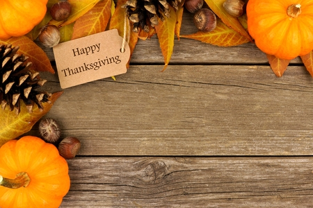 Happy Thanksgiving gift tag with corner border of colorful leaves and pumpkins over a rustic wood background