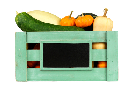 isolated sign: Green wooden harvest crate with autumn vegetables and blank chalkboard label isolated on white