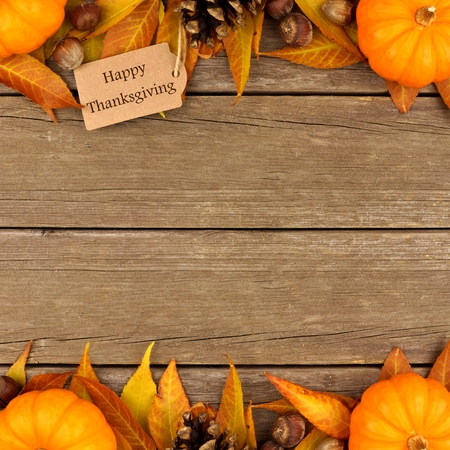 brown background: Happy Thanksgiving gift tag with double border of colorful leaves and pumpkins over a rustic wood background Stock Photo