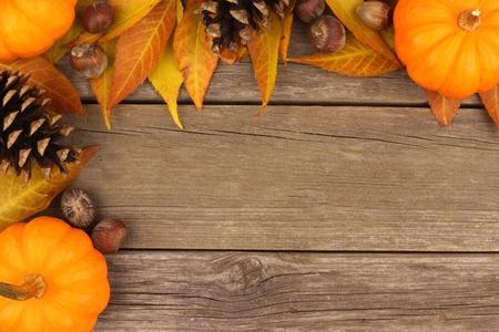 madera r�stica: Frontera de la esquina de oto�o de calabazas, hojas y pi�as de pino sobre un fondo de madera r�stica Foto de archivo