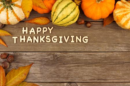 calabaza: Happy letras de madera de Acción de Gracias con una calabaza de otoño y las hojas frontera de la esquina contra la madera vieja