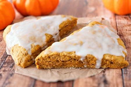 scones: Two sweet autumn pumpkin scones with frosting, on rustic wood background