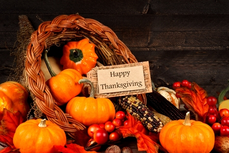Harvest cornucopia close up with Happy Thanksgiving gift tag on dark wood background